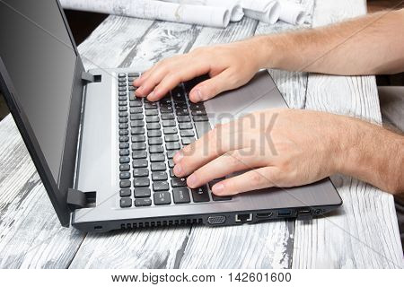 Hands typing numbers on laptop keyboard making online payment at home at the wooden table. On-line shopping concept. Selective focus. Man's hands typing on computer pc keyboard