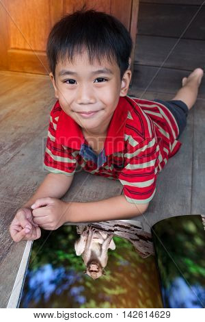 Closeup handsome asian boy smiling and looking at camera. Child reading picture album about animal wildlife lying on wooden floor outdoor at home. Children read and study education concept.