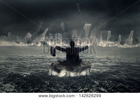 Back view of frustrated businessman sitting on the rock at sea while looking at a sinking city