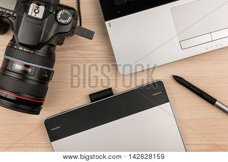 Working table of photographer or artist overhead view wooden surface with laptop and camera