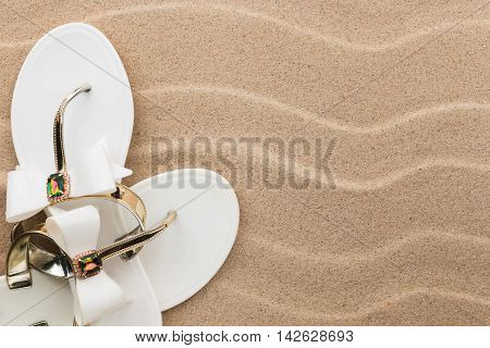 Beach white flip flops encrusted with rhinestones standing on the sand with space for your text