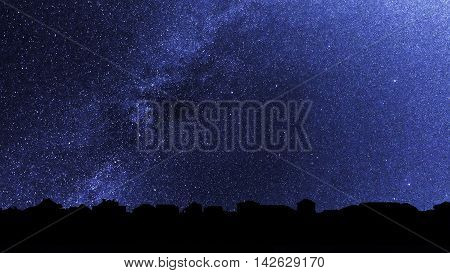 Starry sky over the roofs of suburban houses. Background with millions of stars over the village. Dark skyline in the backlighting.