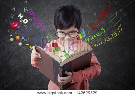 Photo of a little girl standing in the class while reading a book with formula of science math and physics