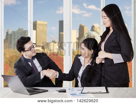 Image of middle eastern businessman shaking hands with indian and chinese businesswomen in the office