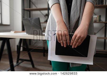 Active business woman with dairy and records. Unrecognizable girl holding notebook, office background. Time-management, planning, scheduling concept