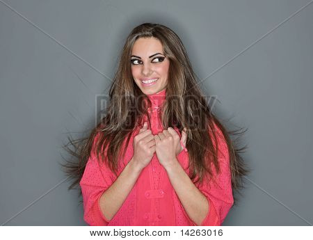 Young Cute Smiling Woman With Long Hairs Dressed In Pink Blouse, Ring Flash Studio Portrait On Gray