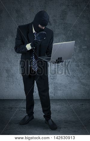 Male thief wearing mask while finding information on the laptop with a magnifying glass