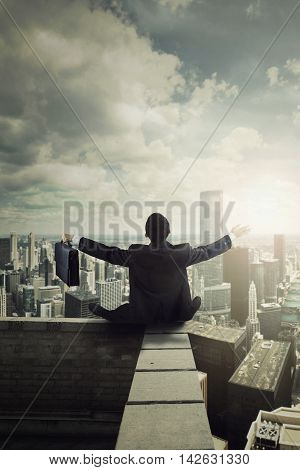 Back view of businessman sitting on the rooftop of the skyscraper building while holding a briefcase