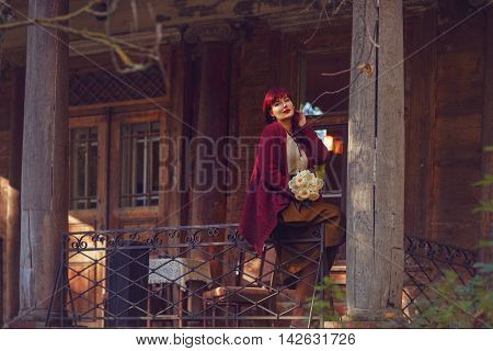 Beautiful young woman with white roses in long skirt and wool red scarf sitting on old house balcony. Early fall. Outside shot. Ambient light.
