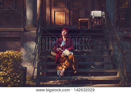 Beautiful young woman in long skirt and wool red scarf sitting on old house stairs holding flowers. Early fall. Outside shot. Ambient light. Copy space.