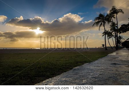 Honolulu, Hawaii, USA - Dec 21, 2015: Setting sun over beach at Ala Moana Park, along Ala Moana Park Drive. The beach overlooks Mamala Bay.