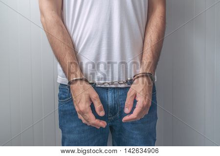 Arrested man with cuffed hands. Unrecognizable male person in jeans with handcuffs held in police station for being suspected of a crime.