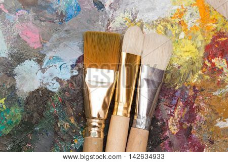 a Paint brushes and old wooden pallet