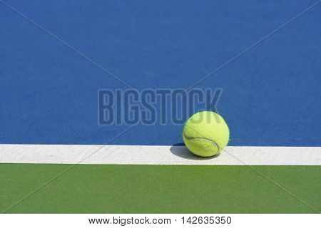 tennis ball on the  blue and green court