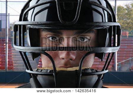 Closeup of a youth baseball catcher with backstop and grandstand in the background.