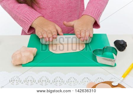 Child hands holding small plunger for mastic dough for cookies
