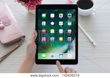 Alushta Russia - July 30 2016: Woman holding in the hand a iPad Pro Space Gray with wallpaper IOS 10 in the screen. iPad Pro was created and developed by the Apple inc.