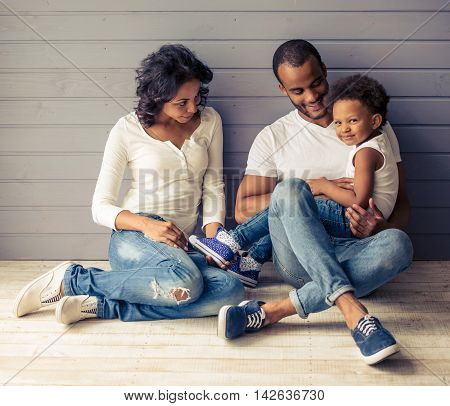 Beautiful young Afro American parents and their cute child are talking and smiling sitting on the floor against gray wall. Girl is looking at camera