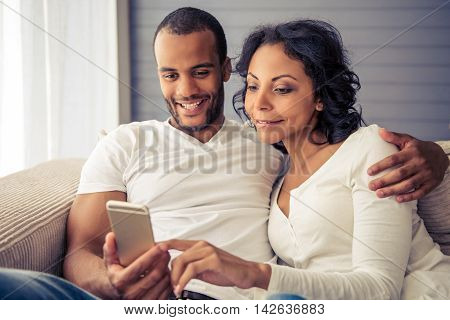 Beautiful young Afro American couple is using a smartphone and smiling while sitting on sofa at home
