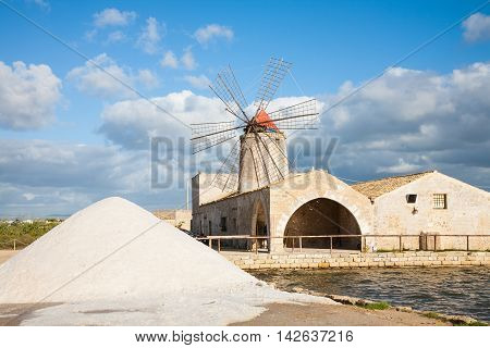 A salt pan windmill and heap of sea salt near Trapani in western Sicily italy