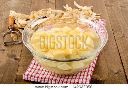 diced potatoes in a glass bowl with water to remove the potato starch