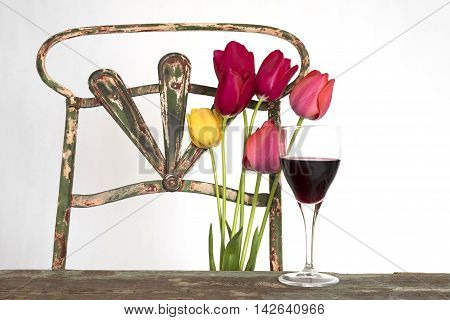 glass of red wine on a wooden table with tulips, old iron chair with tulips in the middle the backrest as background