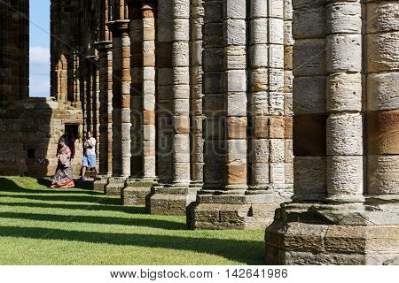 WHITBY ENGLAND - AUGUST 12: Tourists visiting the ruins of Whitby Abbey. In Whitby North Yorkshire England. On 12th August 2016