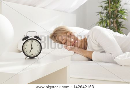 beautiful girl sleeping in her bed. clock on the nightstand. focus on clock