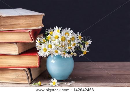 A stack of old vintage books lying on a rustic wooden shelf with a bouquet of daisies in a blue vase. Country still life.