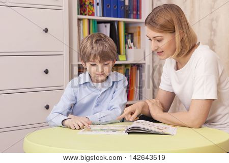 Тeacher teaches the pupil. Sit at the green table. Read the textbook. The show on the page. They smile