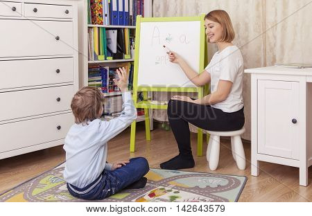 young beautiful woman teacher involved with a student at the blackboard. The teacher shows the board looking at the student smiling. Student sitting on the floor looking at the board raised his hand. Horizontal color image.