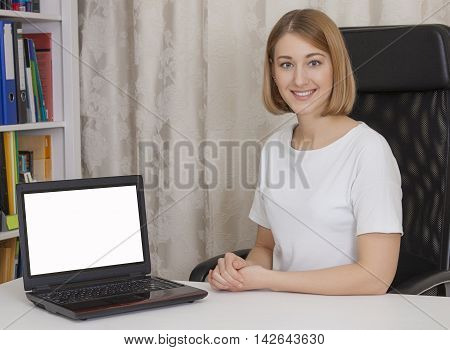 young beautiful business woman sitting at a table with a laptop the screen is turned toward the viewer. Pure white background. color horizontal image