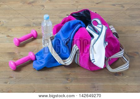 Clothes for sports with pink dumbbells, in the gym on the floor