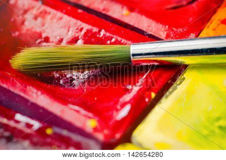 a paint brush with watercolor paints macro