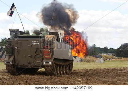 WESTERNHANGER, UK - JULY 25: An M113 APC looks on as a simulated napalm attack is made on VC troops during a Vietnam war battle reenactment at the War & Peace show on July 25, 2015 in Westernhanger