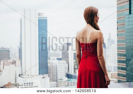 Beautiful Woman In Dress Looking Away From Rooftop In Urban City