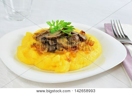Polenta with mushrooms and herbs on white plate
