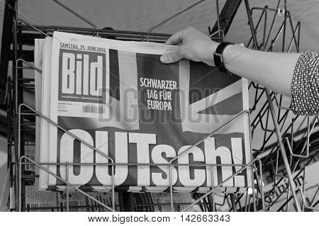 STRASBOURG FRANCE - JUN 25 2016: Woman buying Bild Magazine newspaper with shocking headline titles at press kiosk about the Brexit requesting to quit the European Union