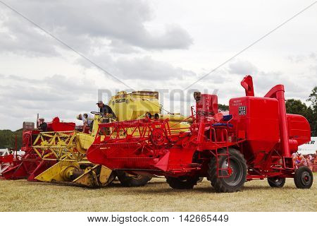 POTTEN END, UK - JULY 27: Vintage combine harvesters line the arena having completed a working display for the watching public at the Dacorum Steam & Country fair on July 27, 2014 in Potten End