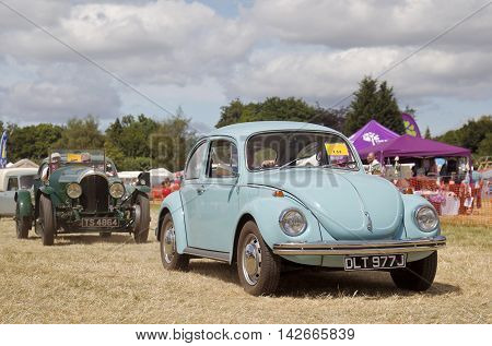 POTTEN END, UK - JULY 27: A classic Volkswagen Beetle motorcar leaves the main display arena having just completed its show to the public at the Dacorum Steam fair on July 27, 2014 in Potten End