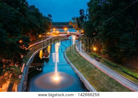 The Scenic View Of Park Watercourse Channel Flowing Into The River Through Stone Bridge. Lighted Walkways, Greenwood Along The Watercourse, Blue Summer Evening Sky Background. Gomel, Homiel, Belarus