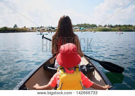 Pretty Young Mother And Little Toddler Son Canoeing In Lake
