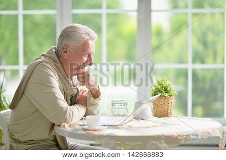 Portrait of a senior man using laptop