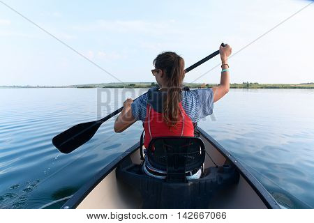 Young lady with long straight brunette hair in sunglasses and life vest paddling the kayak canoeing in the lake on a summer sunny day on blue sky background. Vacation sport hobby.