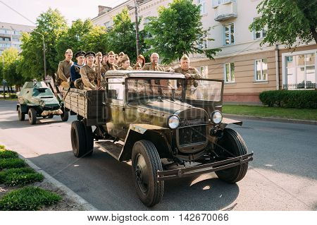Gomel, Belarus - May 9, 2016: Russian Soviet Military Truck ZIS-5V Of WW2 Time With Group People In Soldiers Uniform And Weapon On Board Moving On The Street To Take Part At Victory Day Parade 9 May