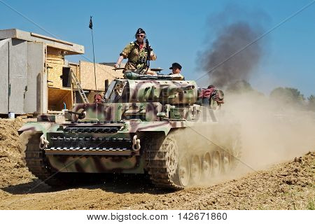 WESTERNHANGER, UK - JULY 18: A replica Panzer III tank speeds around the arena during one of the major WW2 battle reenactments for the public to view at the W&P show on July 18, 2014 in Westernhanger