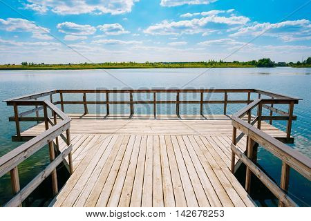 Close View Of Wooden Boardwalk Batten Viewing Platform Area Above The Water Of Lake River In Summer Spring. Panoramic Landscape And Scenic Sky With White Lush Clouds Background.