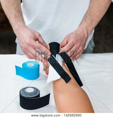 Placing kinesio tape on patient's foot, toned image