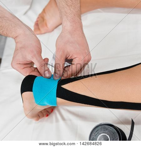 Therapist Using Tape On Sprained Ankle