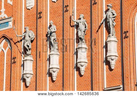 Sculptures On The Facade Of The House Of Blackheads In Riga, Latvia. Famous Landmark. Travel Destination. Town Hall Square. Four Statues Named After Neptune, Agreement, Peace, Mercury.